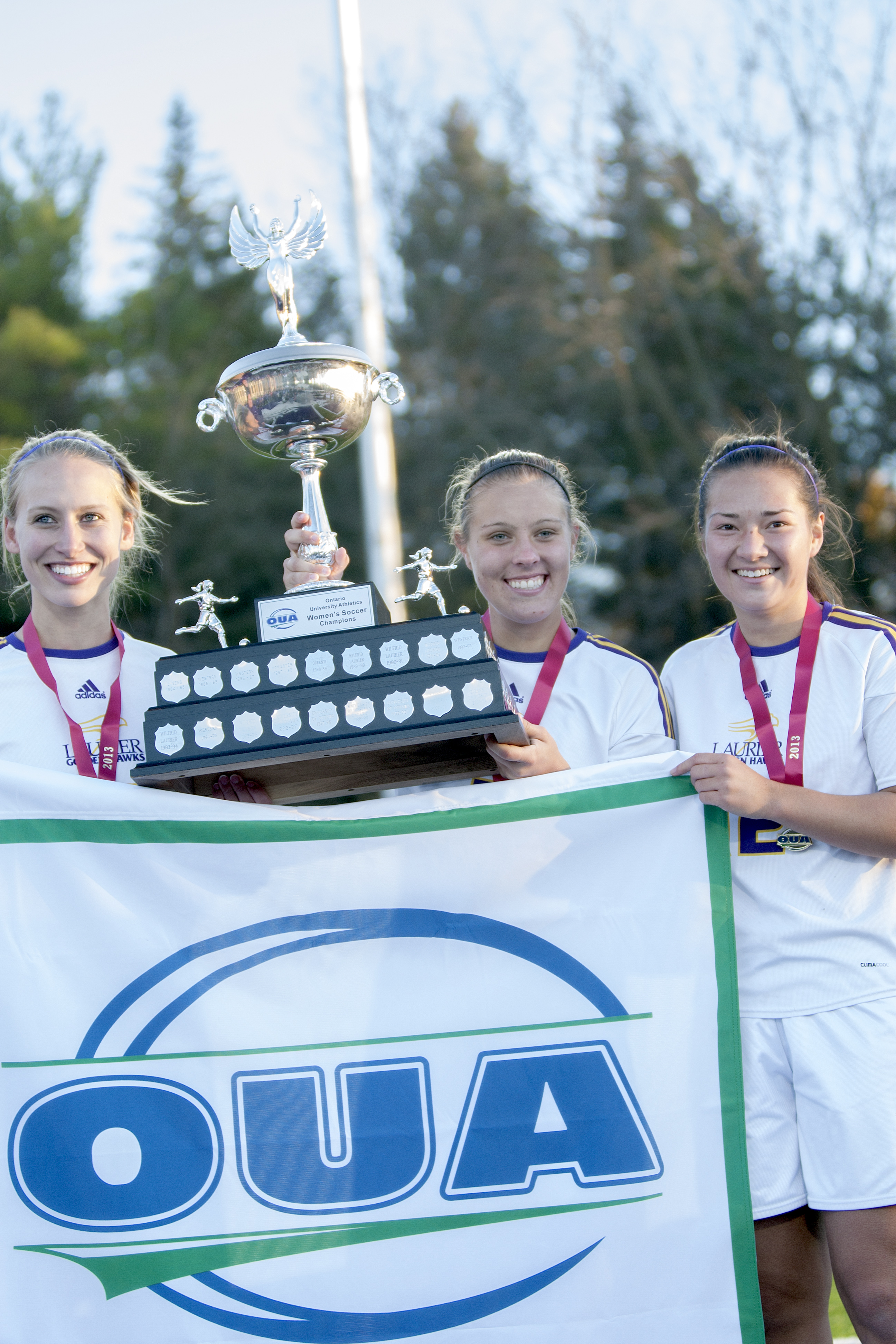 Captains Emily Brown, Kelsey Tikka and Emily Brown hold the championship trophy and banner. (Photo by Heather Davidson)